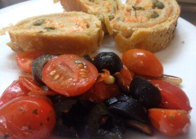 Rollitos de salmón, acompañados de ensalada de tomatitos cherry, olivas negras y piñones